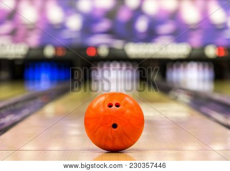 bowling ball ready to roll on a bowling lane with 10 pins in the background