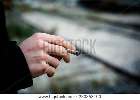 closeup of a young caucasian man outdoors smoking a hand-rolled cigarette or a joint