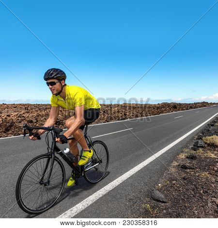 Road biking cyclist man training on bike professional cycling athlete riding racing bicycle in competition race on open road biking with high intensity on highway on workout for triathlon.