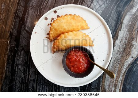 Deep fried meat pastry with hot tomato sauce shot from above
