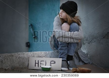 Homeless poor teenage girl sitting outdoors near empty bowl and piece of cardboard with word HELP