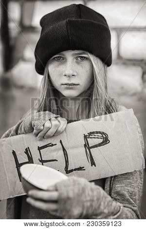 Homeless poor teenage girl holding empty bowl and piece of cardboard with word HELP outdoors