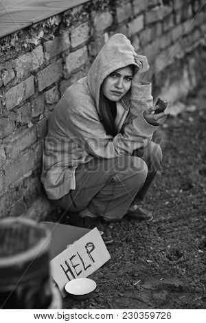 Homeless poor woman sitting outdoors near piece of cardboard with word HELP