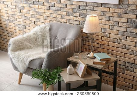 Elegant table lamp and comfortable armchair in room interior near brick wall