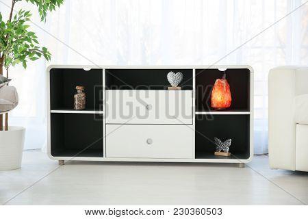 Himalayan salt lamp in shelving unit indoors