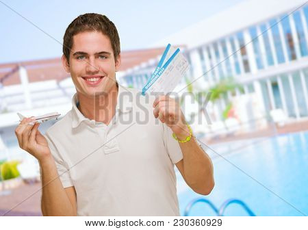 Young Man Holding Boarding Pass And Toy Airplane by a pool