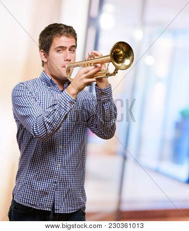 Cute Man Blowing Trumpet against an abstract background