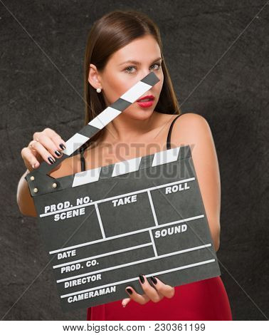 Woman In A Red Dress Holding Clapper Board against a grunge background