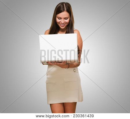 Portrait Of A Young Woman Holding A Computer against a grey background