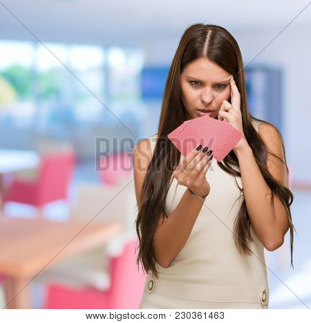 Confused Young Woman Holding Playing Cards in a restaurant