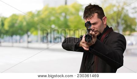 Man aiming with rifle against a street background