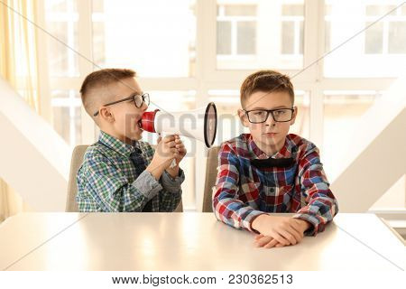 Funny little boy with megaphone shouting at his bored friend sitting at table