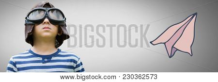 Digital composite of Boy against grey background with pilot goggles and hat