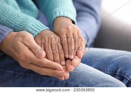 Woman and adopted African-American child, closeup of hands