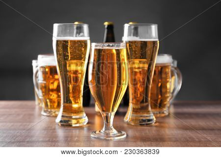 Glassware with fresh beer on wooden table