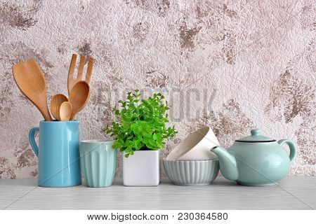 Different cooking utensils with dishware on table
