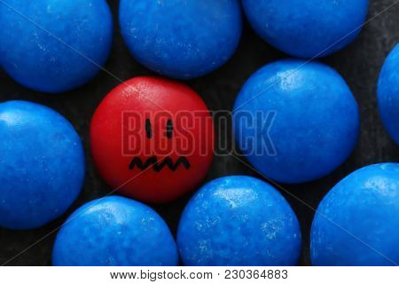 One red drop with painted sad face among blue ones. Difference and uniqueness concept