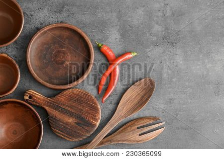 Cooking utensils and chili peppers on grey background