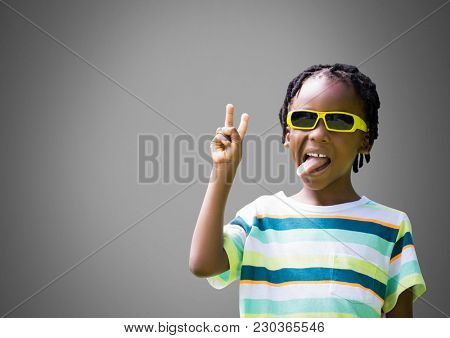 Digital composite of Cheeky Boy against grey background with sunglasses sticking out tongue