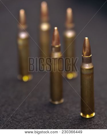 Five .223 caliber rounds on a black background poster
