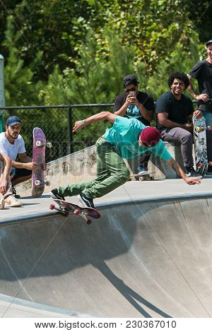 Suwanee, Ga - September 2017:  A Young Adult Skateboarder Drops In At The Bowl As Other Skateboarder
