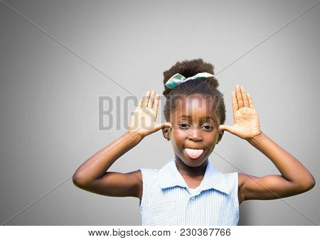 Digital composite of Girl against grey background making funny face sticking out tongue