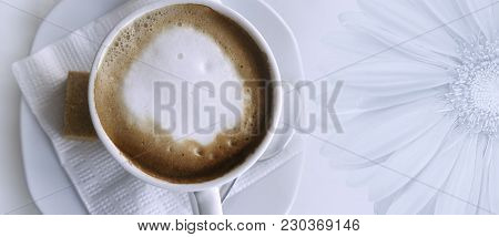 Coffee Cappuccino In A White Cup On A White Napkin And Saucer.  Place For Text With A Large Gerbera