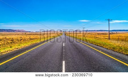 Long Straight Road through the Endless wide open landscape of the semi desert Karoo Region in Free S