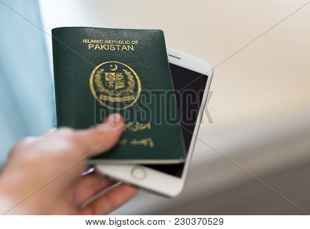 A Hand Holds Pakistan Passport. Focus On The Font On Passport.