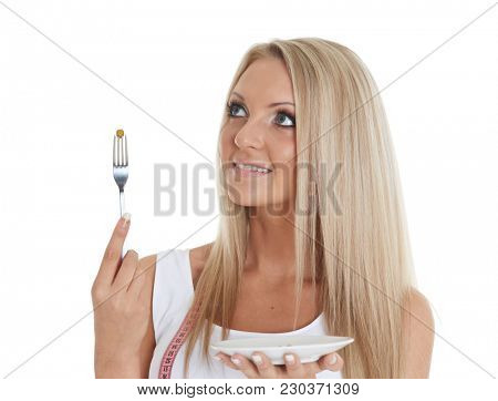 Slender young woman holding a fork with a pea and tape measure on a white background. Concept of dieting.