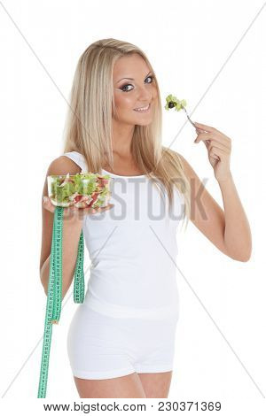 Slender young woman with tape measure holds a bowl of salad  on a white background. Concept of dieting.