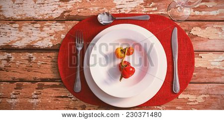 Overhead view of tomatoes served in plate on wooden table