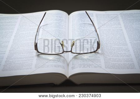 Eyeglasses On An Opened Text Book