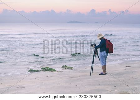 Photographer Taking A Photograph On The Beach