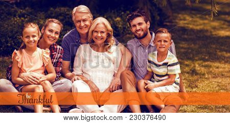 Thanksgiving greeting text against portrait of multi generation family relaxing on grass