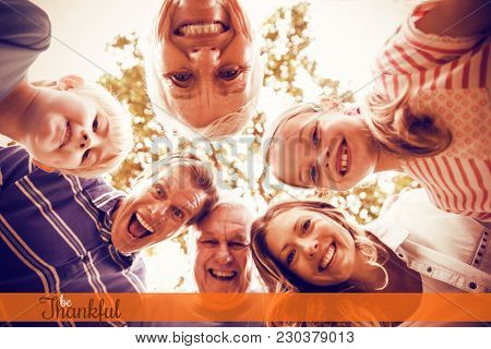 Thanksgiving greeting text against portrait of happy multi-generation family forming a huddle in park