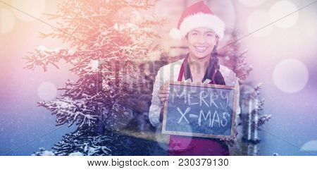 Snow covered trees during winter against pretty waitress with merry x-mas written on chalkboard