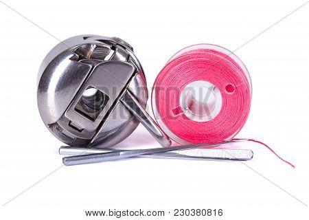 Bobbin Case, Plastic Bobbin And Sewing Machine Needles On White Background