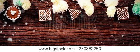 Snow falling against various christmas cookies and decorations on table