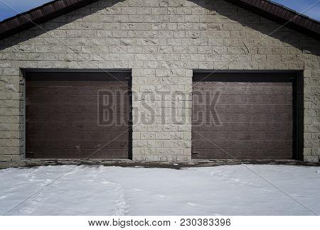 Garage doors. Garage. New garage. Brown garage doors. Grunge garage. Grey wall. Brown door.