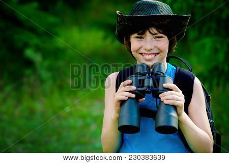 Ten year old boy go hiking with backpack and binocular. Exploring the world. Summer holidays. Outdoor activities.