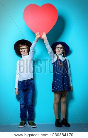 Happy pre-teen boy and girl holding big red heart over blue background. Friendship. First love. Valentine's Day.