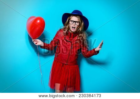 Pretty ten-year-old girl holding heart shaped balloon over blue background. Valentine's Day. Children's fashion.