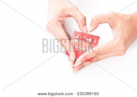 Woman's Hands With Condom And Heart Shape Hand Sign, Love And Safe Sex Concept