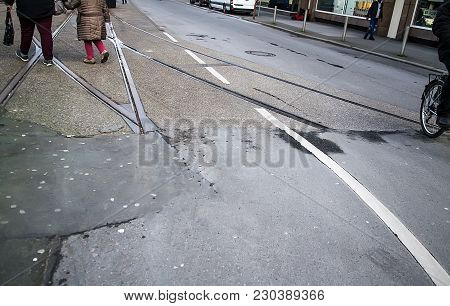 Crossing Tram Rails On The Dirty Street Asphalt With Sticked Chewing Gums
