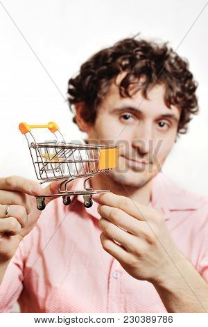 Curly-haired Young Man Holding A Small Cart To The Supermarket. Shopper, Shopping, Store, Inflation,