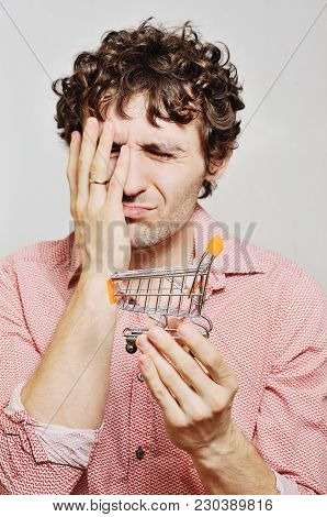 Curly-haired Guy With A Small Trolley For A Supermarket In Their Hands. Financial Constraints, Risin