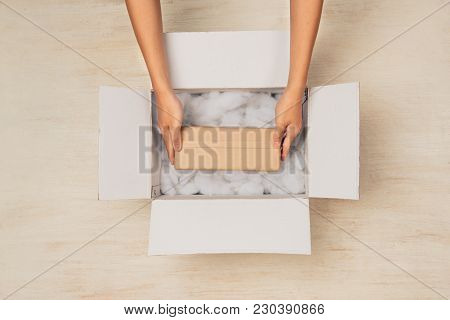 Opening A Carton Box. Hands Holding Gift Box In Cardboard Box
