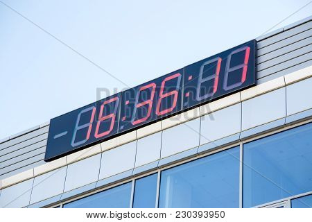 Photo Of Electronic Clock On Building In Afternoon Against Blue Sky Background