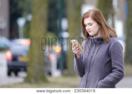 Young Woman Checked Her Cell Phone For New Messages Outdoors